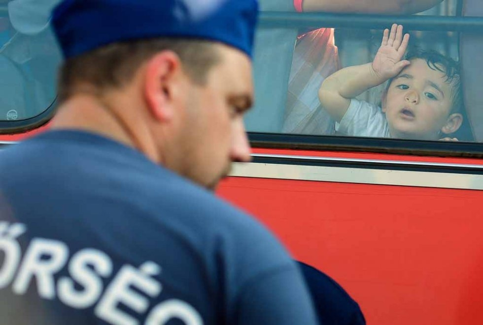A child presses his faces against the window on a police bus at a collection point of the Hungarian police near Roszke village of the Hungarian-Serbian border on August 27, 2015 (AFP photo / Attila Kisbenedek)