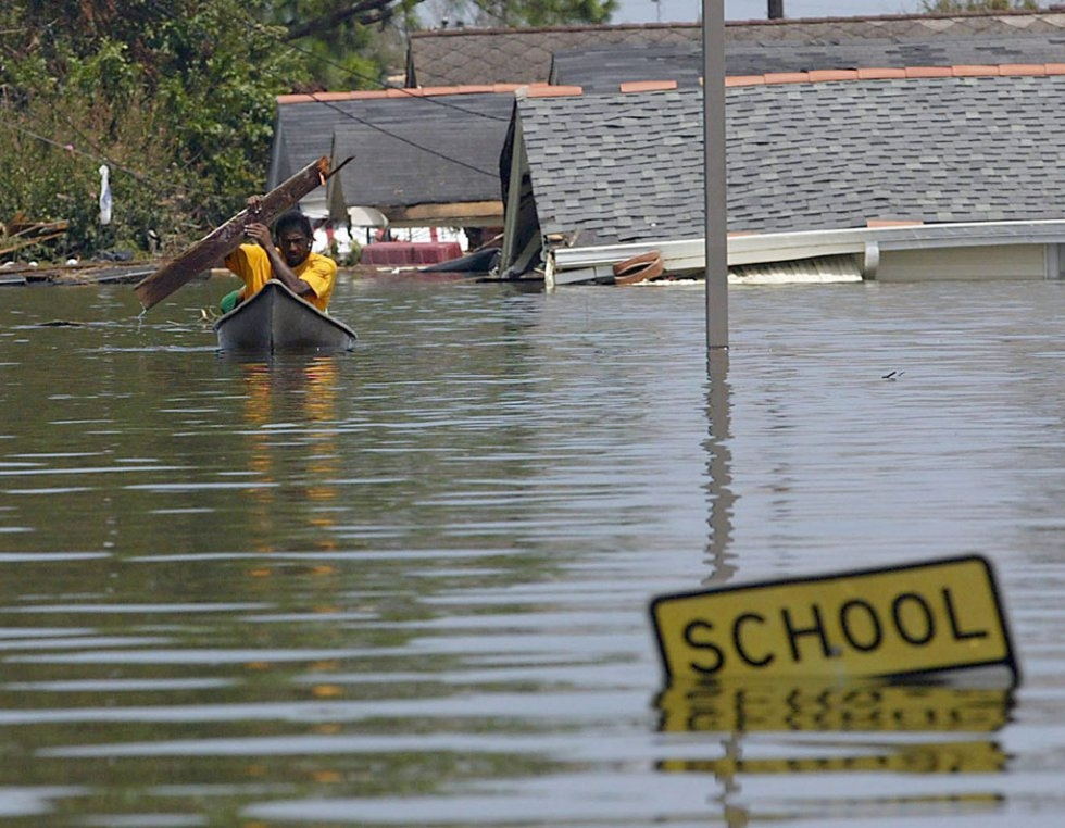 A resident uses a board to paddle through flood waters in New Orleans on August 30, 2005 following Hurricane Katrina (AFP Photo / James Nielsen)