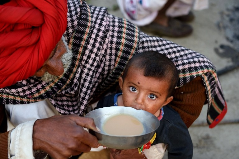 Nomadic shepherd Padma Ram helps his nine-month-old granddaughter Anu drink tea at his camp in Sikri in Faridabad on March 25, 2015