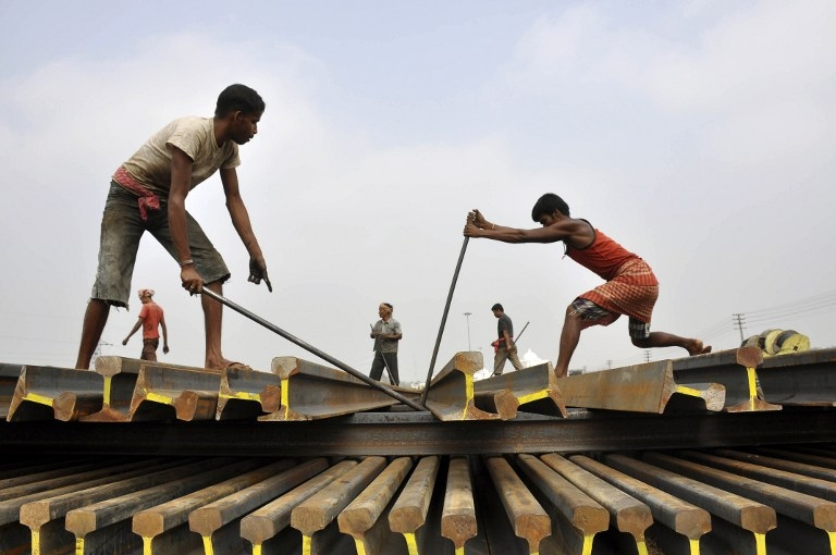 Labourers stack railway tracks at a station in Agartala, eastern India, on February 26, 2015