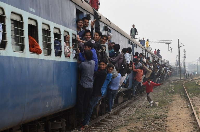 Passengers hang onto a train on the outskirts of New Delhi on February 25, 2015