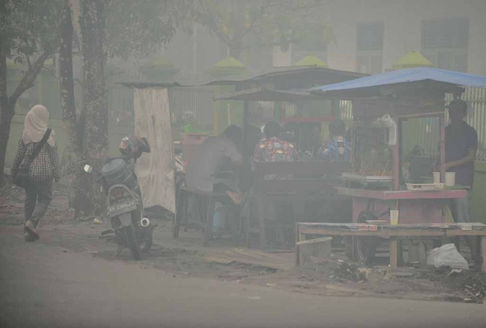 People eat breakfast at a roadside stall shrouded in haze in downtown Palangkaraya in late October.