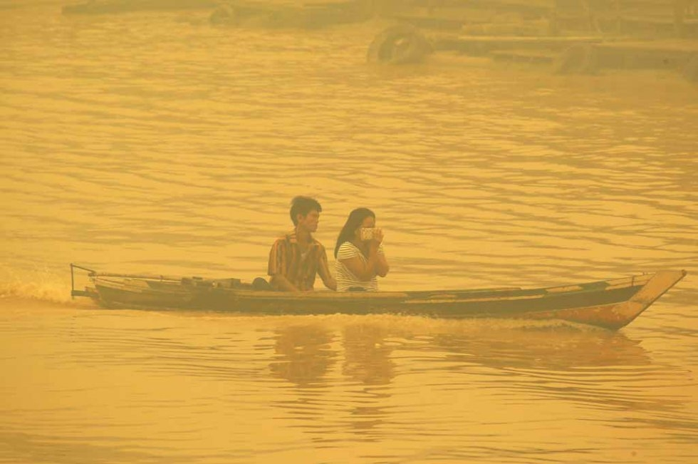 A couple crosses the river in Palangkaraya in October.