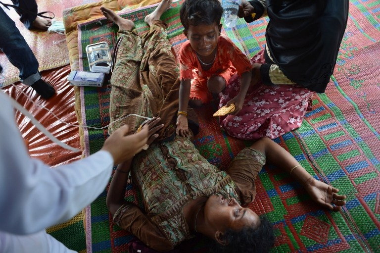 Four-year-old son Abdul Hakim weeps as his mother Ambihatu, a 21-year-old Rohingya woman from Myanmar, is treated for malnutrition at a confinement area at Bayeun in Indonesia's Aceh province on May 21, 2015