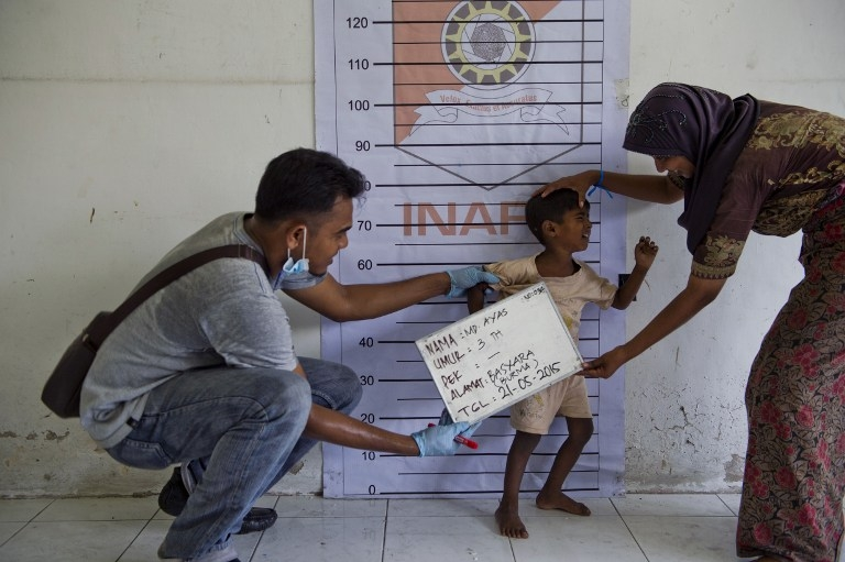 A Rohingya boy from Myanmar is photographed during police identification procedures at a newly set up confinement area in Bayeun, in Indonesia's Aceh province