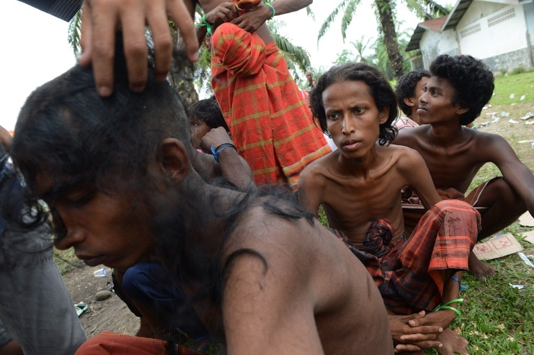 Rohingya men from Myanmar, among a group of 400 rescued off the Indonesian coast, receive haircuts at a confinement area in Bayeun, Aceh province on May 22, 2015