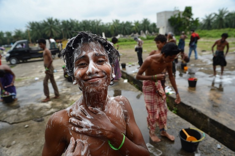 Rohingya youths from Myanmar, among a group of 400 rescued on May 20, wash themselves at a confinement area for migrants at Bayeun, Aceh province on May 22, 2015
