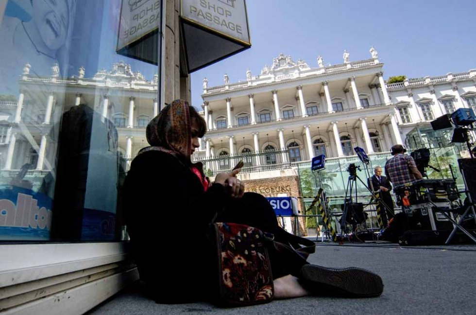 A journalist waits outside the Palais Coburg Hotel in Viennan on July 3, 2015.