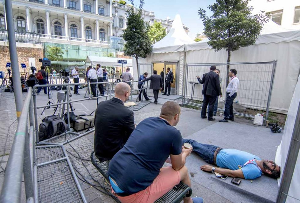 A journalist rests outside the Palais Coburg Hotel in Vienna on July 3, 2015