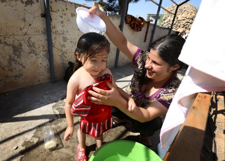 An Iraqi Christian refugee bathes her daughter in the yard of a church near Arbil on August 12, 2014