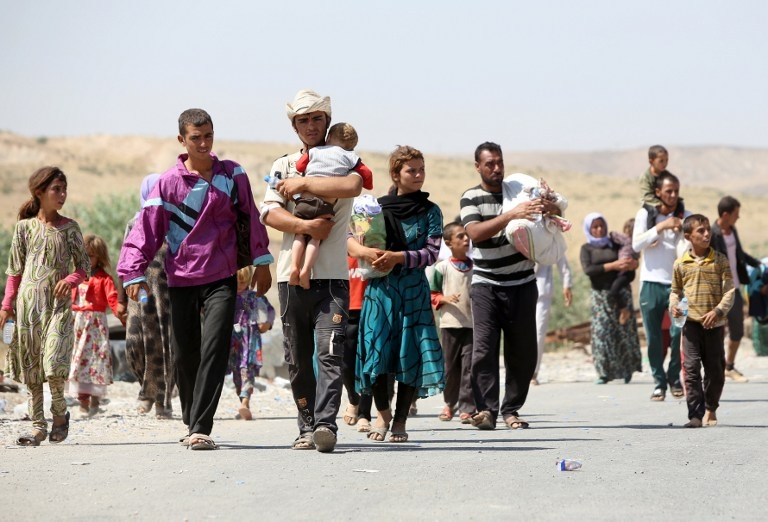 Yazidi Iraqis fleeing the Islamic State group cross into Syria at Fishkhabur on August 11, 2014