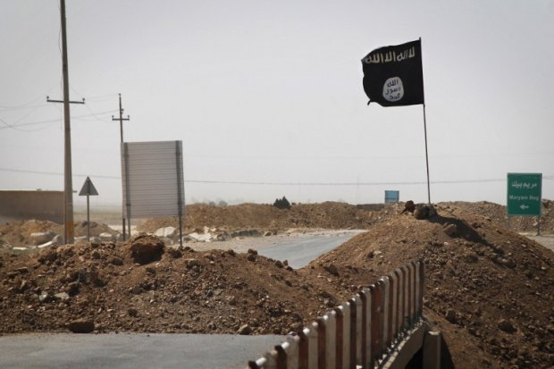A flag of the Islamic State (IS) is seen on the other side of a bridge at the frontline of fighting between Kurdish Peshmerga fighters and Islamist militants in Rashad, on the road between Kirkuk and Tikrit, on September 11, 2014 (AFP Photo / JM Lopez)