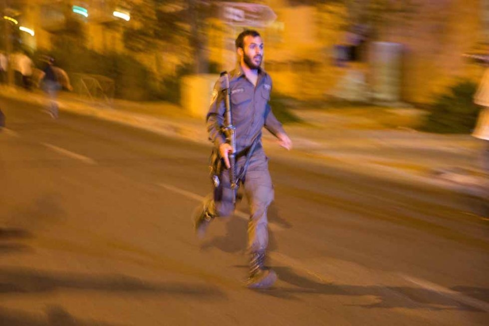 An Israeli policeman rushes to the site of a stabbing near Jerusalem's central bus terminal.