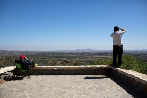Israeli civilians stand near Mount Bental, in the Israeli-annexed Golan Heights, as they watch through binoculars the fighting between Syrian government troops and Islamist rebel fighters on September 2, 2014