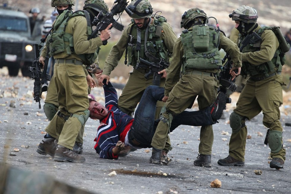 Israely soldiers detain a wounded Palestinian stone thrower during clashes in Beit El, on the outskirts of the West Bank city of Ramallah, on October 7, 2015 (AFP / Abbas Momani)