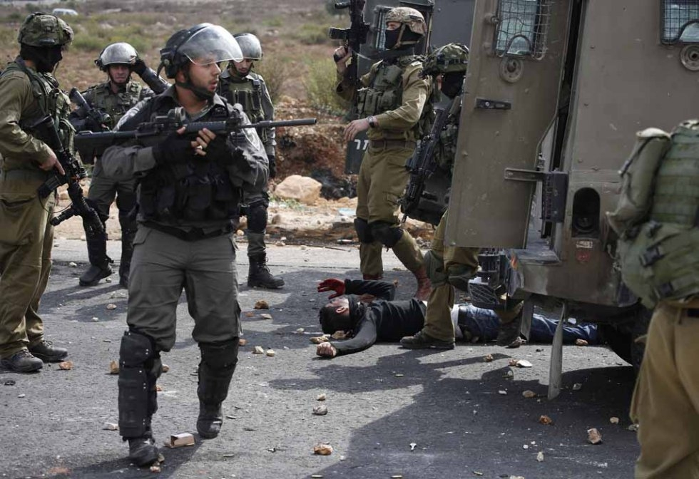 Israeli soldiers and border guards stand next to a wounded Palestinian stone thrower who was shot by infiltrated members of the Israeli security forces during clashes in Beit El on October 7, 2015 (AFP / Abbas Momani)