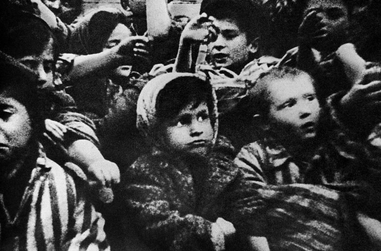 Child survivors of the Auschwitz concentration camp show their tattoos in January 1945