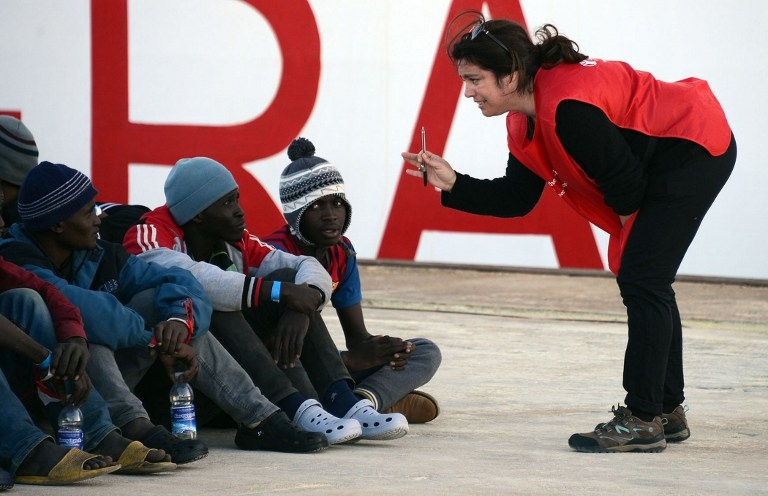 Shipwrecked migrants listen to an Red Cross worker after disembarking from a rescue vessel in the port of Augusta in Sicily on April 16, 2015