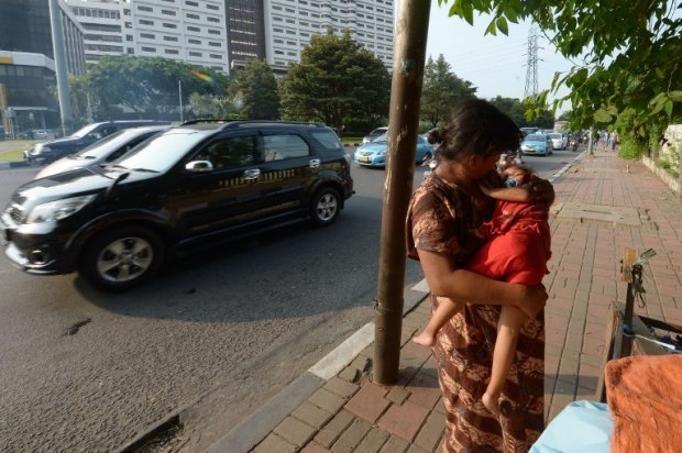 Indonesian homeless Rini cradles her daughter Ifah on a sidewalk in Jakarta on April 29, 2014