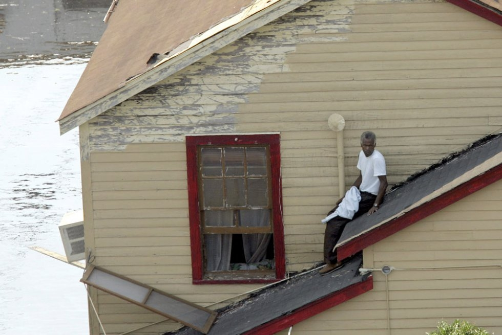 A man waits to be rescued from a roof as flood waters continue to rise on September 2, 2005 in New Orleans