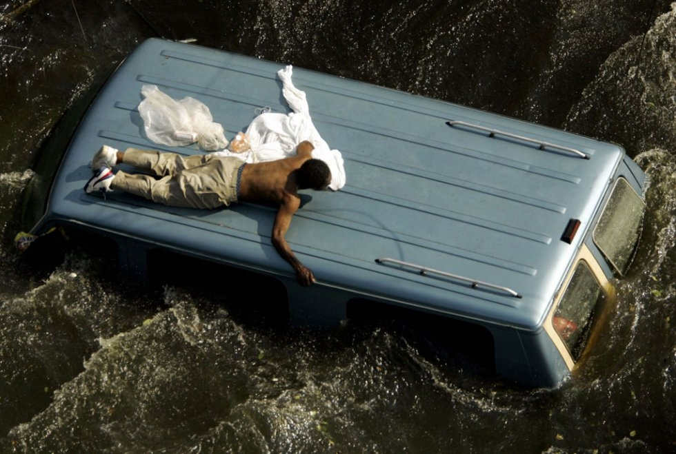 A man clings to the top of a vehicle prior to being rescued by the US Coast Guard from the flooded streets in the aftermath of Hurricane Katrina in New Orleans, Louisiana, 04 September, 2005. (AFP Photo / pool / Robert Galbraith)