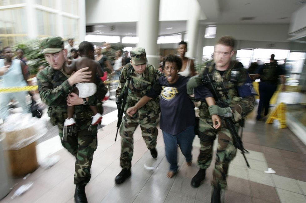 A woman in shock is helped by Louisiana National Guardsmen after gunshots were heard at New Orleans Superdome on September 1st