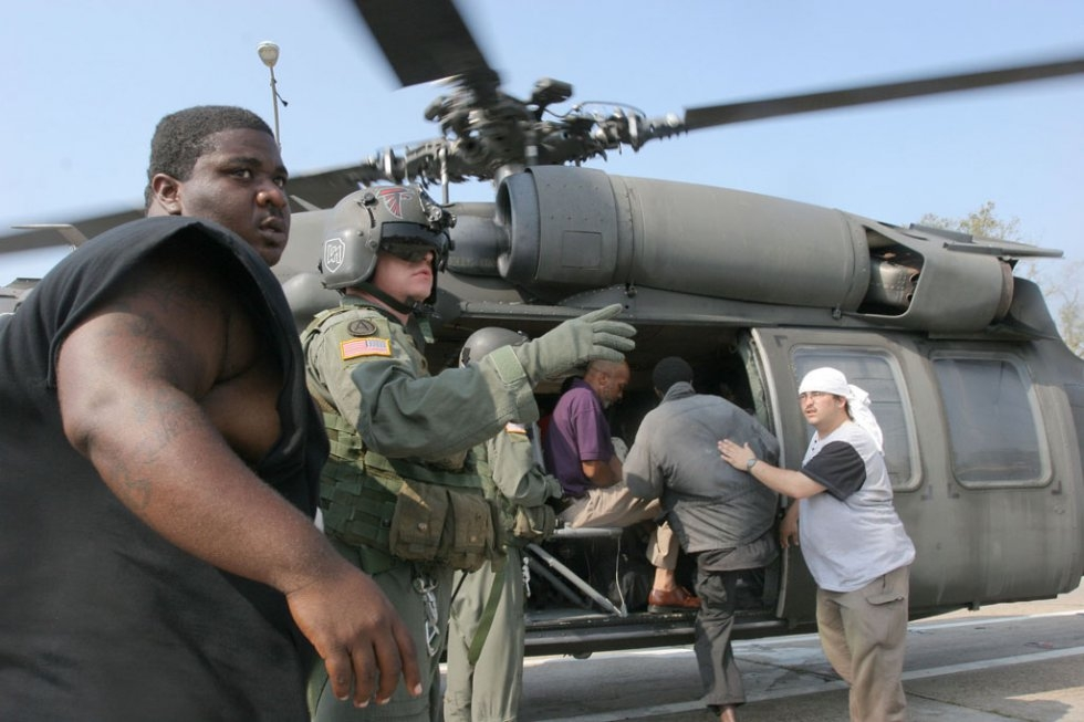 A US Army soldier and a New Orleans deputy sheriff direct stranded people to board a helicopter on near the Superdome in New Orleans on September 2, 2005