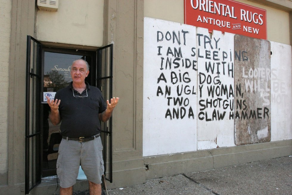 Rug store owner Bob Rue speaks in front of his shop adorned with graffiti warning looters away in New Orleans on September 4, 2005