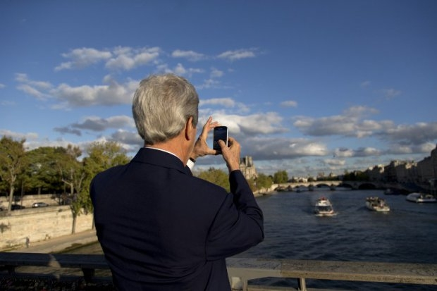 U.S. Secretary of State John Kerry pauses to take with his mobile phone a photograph of the Seine river from the Passerelle Léopold-Sédar-Senghor walking bridge in Paris on October 13, 2014 (AFP Photo / pool / Carolyn Kaster)