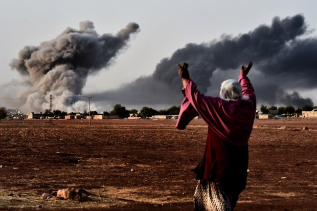 A woman reacts as smoke rises from Kobane on October 13, 2014