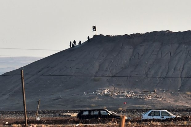 Alleged Islamic State group militants stand next to an IS flag atop a hill in the Syrian town of Kobane, as seen from the Turkish-Syrian border (AFP Photo / Aris Messinis)
