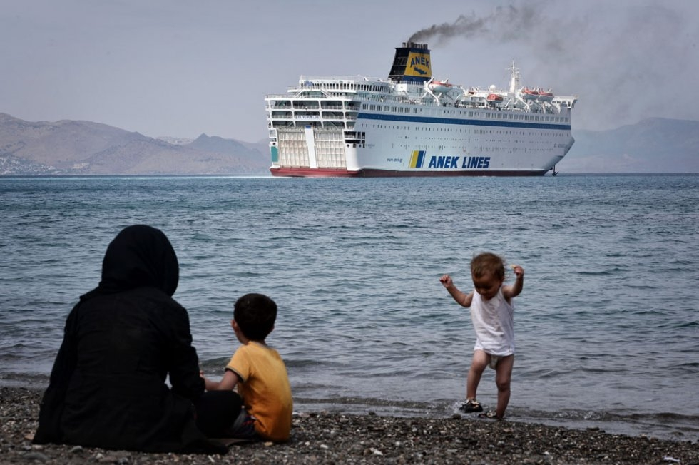 Syrians watch a ferry arriving at the port of Kos on August 14, 2015