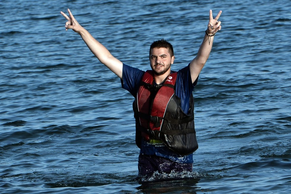 """A Syrian man flashes the V-sign after swimming to the shores of Kos from a half-sunk dinghy on August 17, 2015"