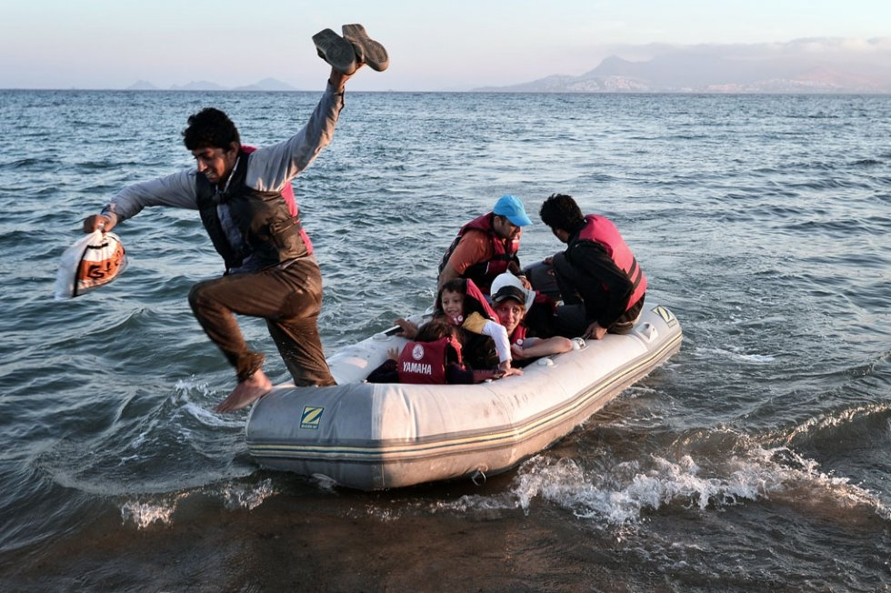 A migrant jumps off a small dinghy after arriving to the shores of the Greek island of Kos from Turkey on August 18, 2015