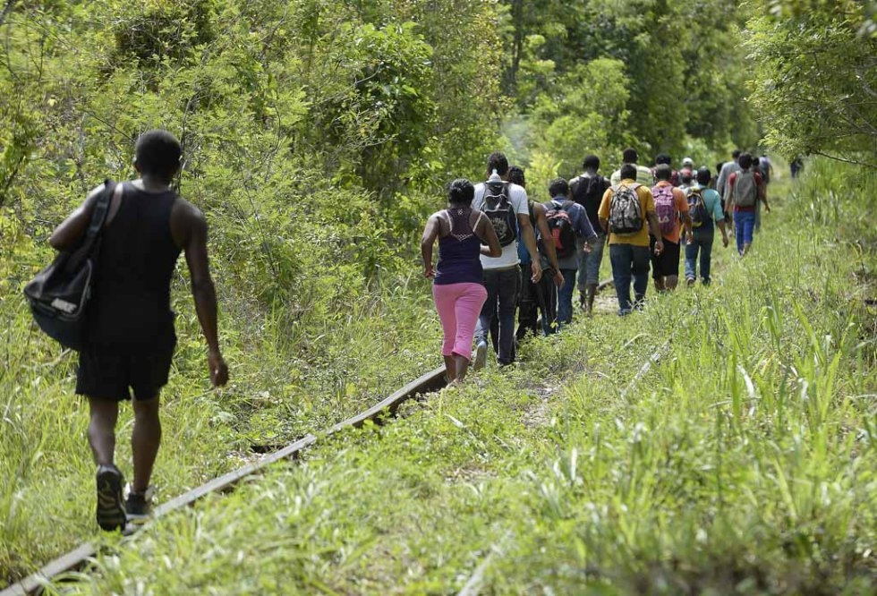 Migrants walk along the train tracks in Palenque, Chiapas State on June 19, 2015