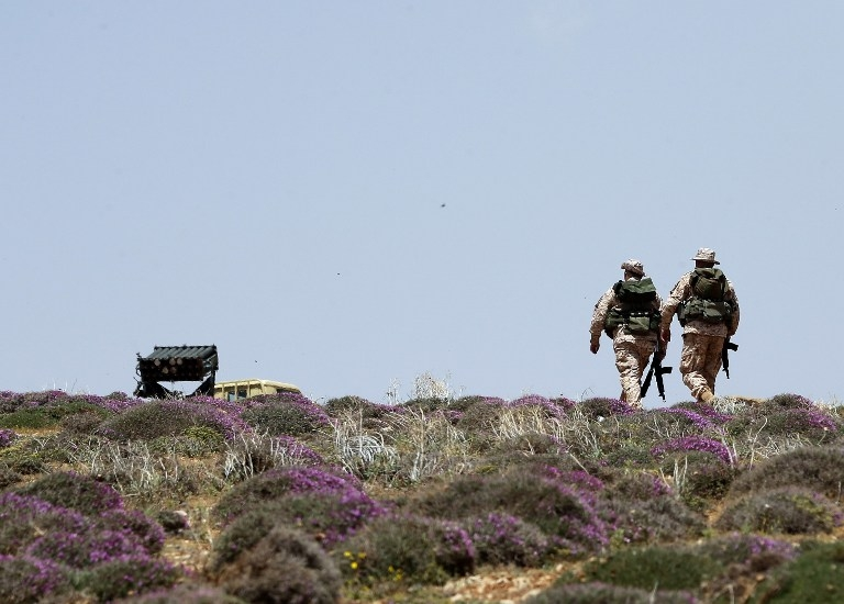 Two Hezbollah fighters patrol a hill on the Lebanese side of the Qalamun mountains on May 20, 2015