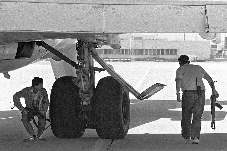 Two hijackers inspect the underside of the TWA Boeing in Beirut on June 19, 1985