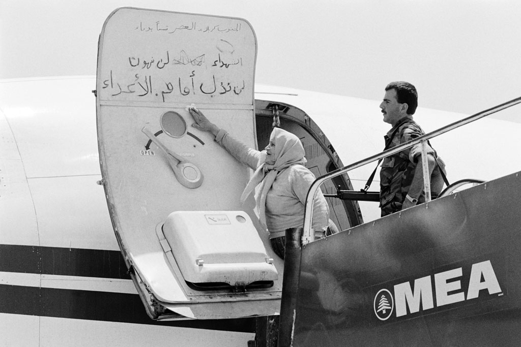 A Lebanese woman cleans off slogans written by hijackers on the door of the hijacked TWA plane, on July 6, 1985 at Beirut airport