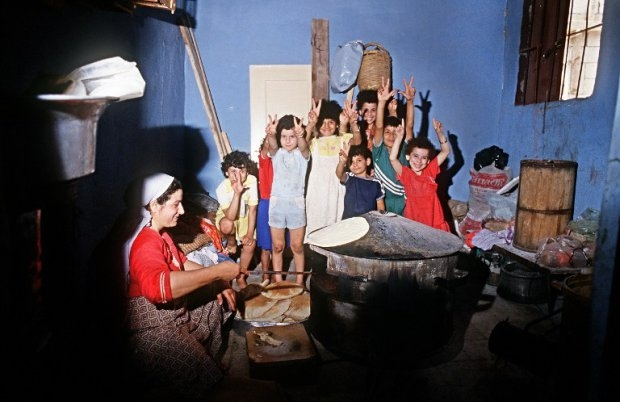 Palestinian children make the victory sign while a woman cooks bread in the refugee camp of Shatila,near Beirut, June 23, 1985
