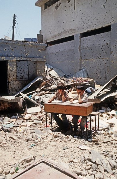 Palestinian children study in the courtyard of the school of the refugee camp in Shatila,near Beirut, 23 June 1985.