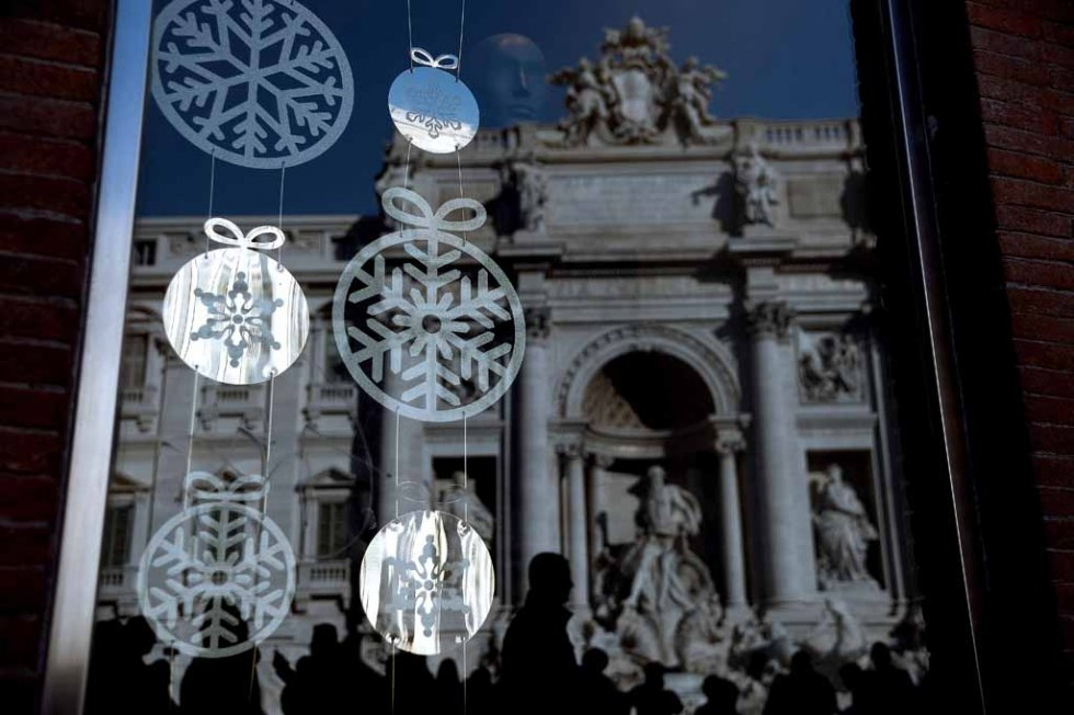 Trevi Fountain reflected in a window shop. December, 2015.