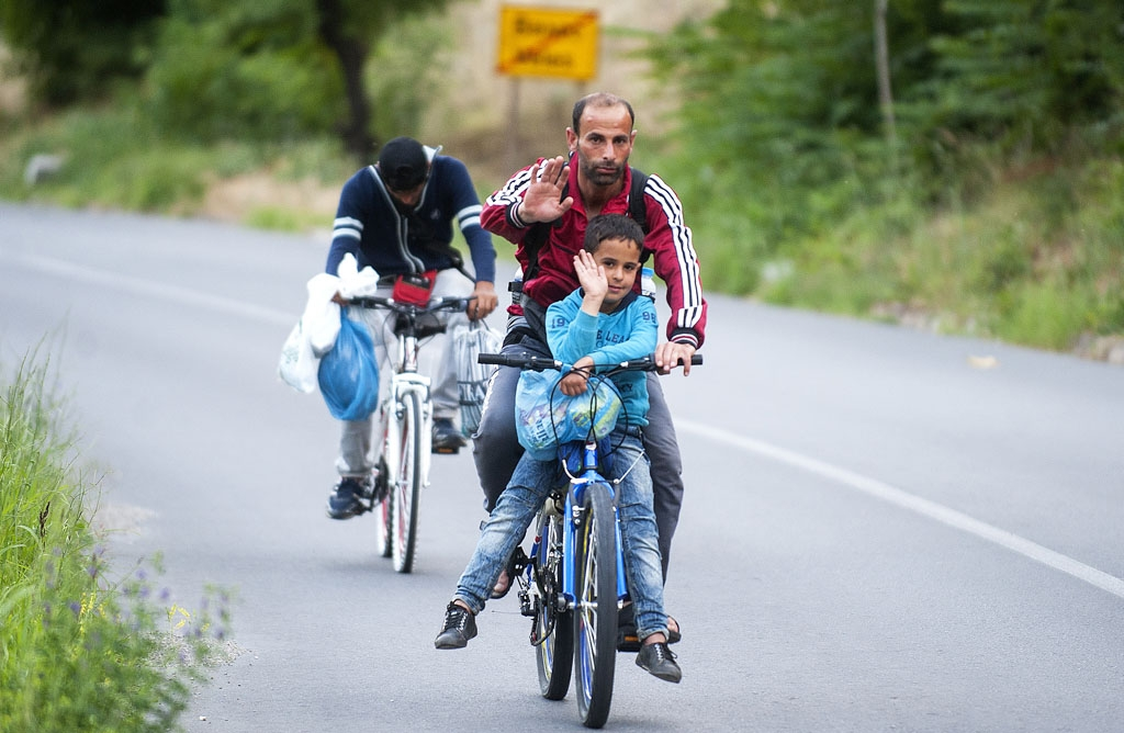 A migrant and his son ride a bicycle on a highway near the town of Veles on June 9, 2015
