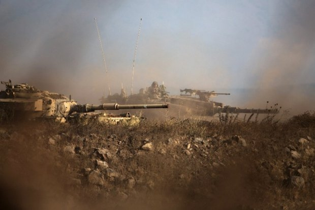 An Israeli soldier sits in his Merkava tank on alert position on the Israeli-annexed Golan Heights near the Quneitra crossing with Syria, on September 1, 2014