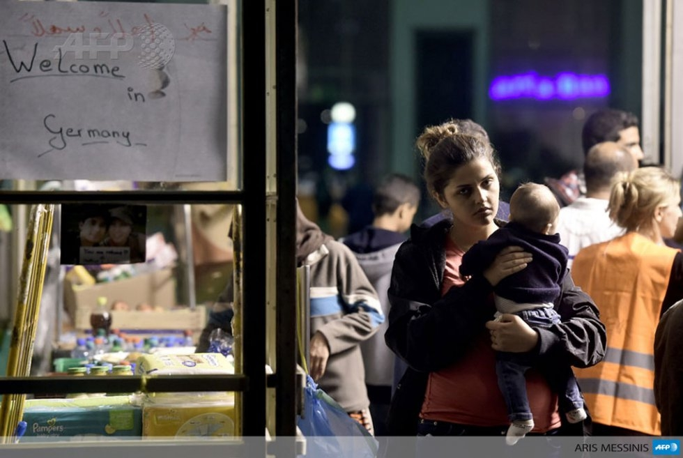 Alia and her baby wait at a makeshift registration office in Munich, on Sept. 3, 2015 (AFP Photo / Aris Messinis)