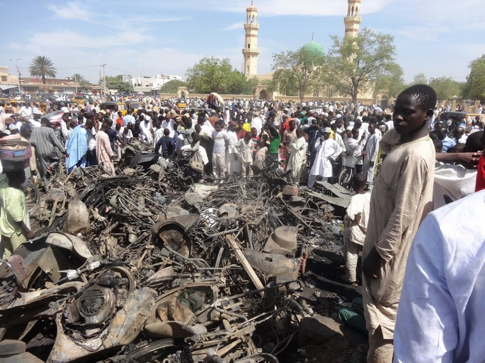 Residents outside the central mosque in Kano a day after gunfire and suicide blasts killed at least 120 people there.