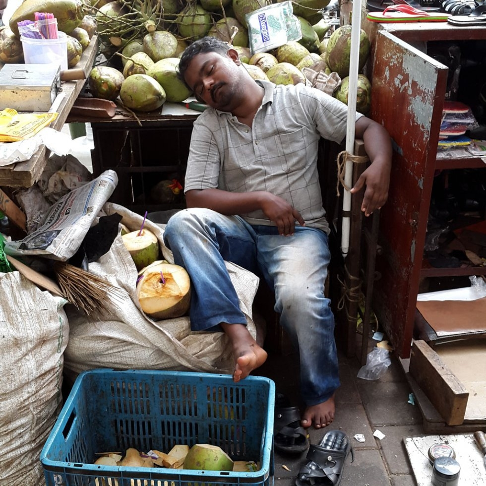 """I had stepped down the road from our office to have a cup of tea when I saw the guy enjoying a siesta….. He was awakened by a fellow shopkeeper as I started to shoot so I walked away. But I sensed that he would doze off again. I came back 5 minutes lat"