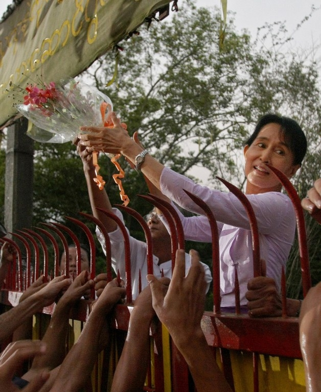 Suu Kyi takes flowers from supporters after her release from house arrest in 2010.