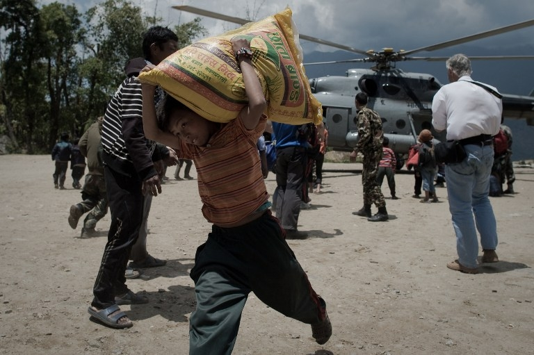 A boy carries a sack of rice from an Indian Air Force Helicopter in the village of Barpak in north-central Nepal on May 4, 2015