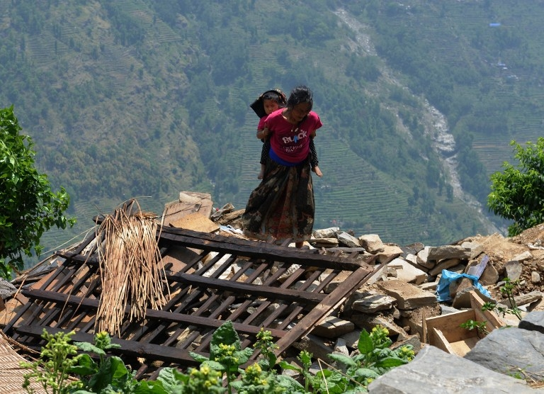 A Nepalese woman carries a child on her back past damaged homes in a village northwest of Kathmandu on May 11, 2015