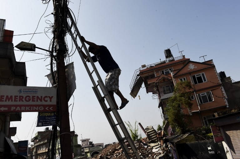 A Nepalese man climbs down a ladder in Kathmandu on May 1, 2015, after fixing some wiring near a house left precariously standing after the April 25 quake
